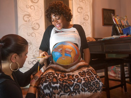 Xiomara Babilonia, owner of XS Artistry in Pennsauken, paints the belly of Salena Ross of Camden, who is eight months pregnant.  04.29.16