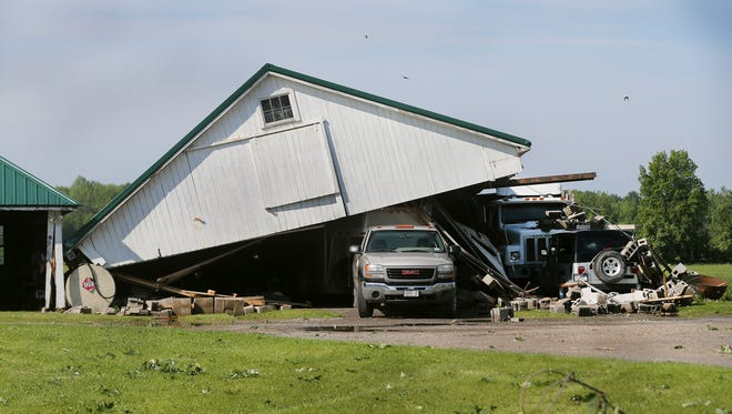 A barn roof was blown onto several vehicles at Gerlock Farm in Farmington after a tornado touched down on June 10, 2015.