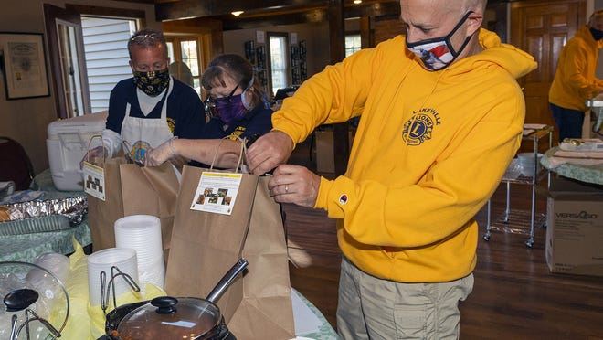 Lakeville Lion Christopher Plonka, front, packages up a to-go meal, while Mark Dube and Diana McCue work on the side dishes, Saturday duing the Lions' Take Out Dinner fundraiser.