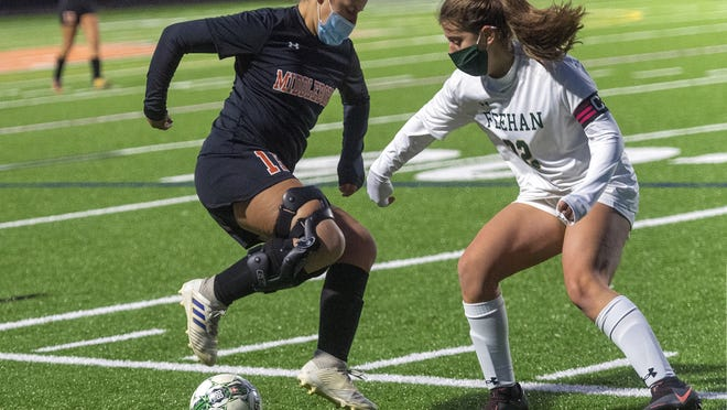 Middleboro's Aria Baken mixes it up along the sideline with Bishop Feehan captain Lindsey Moskal Monday night during high school soccer action at Middleboro High School. Feehan to the win, 4-0, but the Sachems are still holding strong on the season with a 6-2 record.