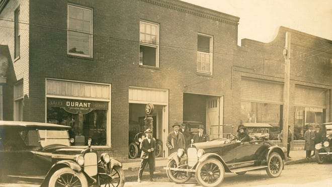 Edith Vanderbilt sits in a brand-new Durant outside a dealership, possibly in Asheville.