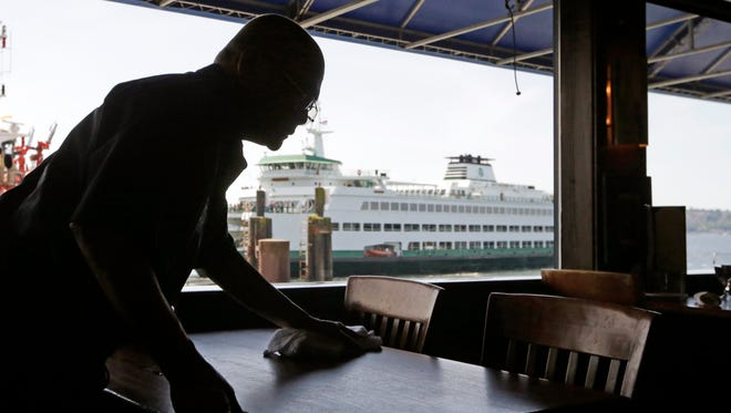 A worker cleans a table at a restaurant in view of a nearby docked state ferry on the Seattle waterfront on May 14, 2014.