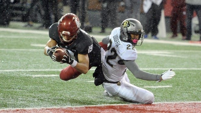 Washington State Cougars wide receiver Brandon Arconado (19) scores a touchdown against Colorado Buffaloes defensive back Trey Udoffia (22) during the first half at Martin Stadium.