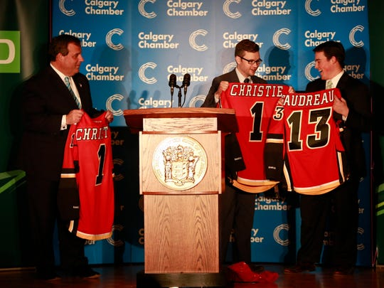Gov. Chris Christie and his son, Andrew, get Calgary Flames jerseys after the governor's keynote address at the Energy Sector Luncheon, hosted by the Calgary Chamber of Commerce, at the Petroleum Club in Calgary, Alberta, Canada on Thursday, Dec. 4, 2014. (Governor's Office/Tim Larsen)