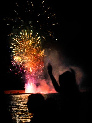 Young spectators raise their hands during the fireworks display June 30 at the annual Clyde Festival by the Lake.