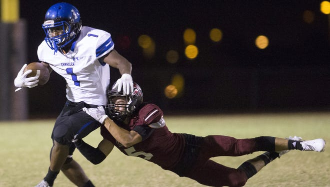 Mesa Red Mountain corner back Carter Liu attempts to tackle Chandler WR/RB Ryan Johnson (1) during a high school football game at Red Mountain High School on August 19, 2016.