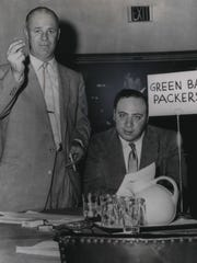 Packers coach Ray (Scooter) McLean (left), with Packers chief scout Jack Vainisi, raises his hand in making the first choice in the 1959 NFL draft in Philadelphia. The Packers chose Randy Duncan of Iowa.