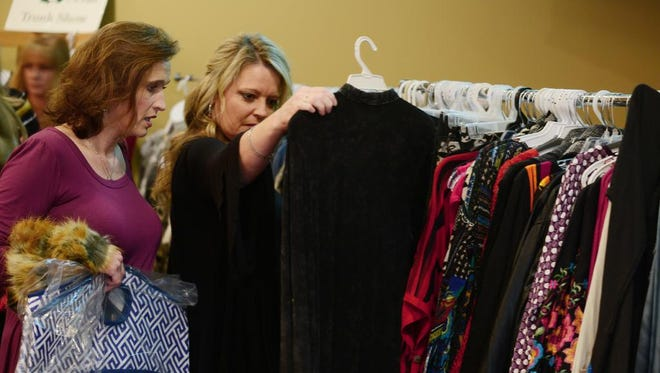 Shea Thweatt and Rosy Roberts (left to right) look at clothing during the Women in Business Holiday Luncheon at Union University's Carl Grant Events Center on Thursday.