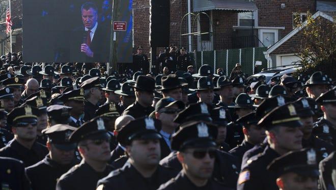 Police officers turn their backs as New York City Mayor Bill de Blasio speaks at the funeral of officer Rafael Ramos on Saturday.