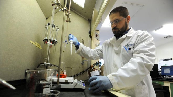 In this file photo, Richard Gualandi works with liquid samples at a biofuels testing lab at Asheville-Buncombe Technical Community College's Enka campus.