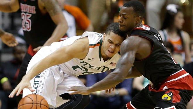 Miami guard Manu Lecomte (20) drives up against Louisville guard Chris Jones (3) during the second half of an NCAA college basketball game, Tuesday, Feb. 3, 2015, in Coral Gables, Fla. Louisville defeated Miami 63-55. (AP Photo/Wilfredo Lee),