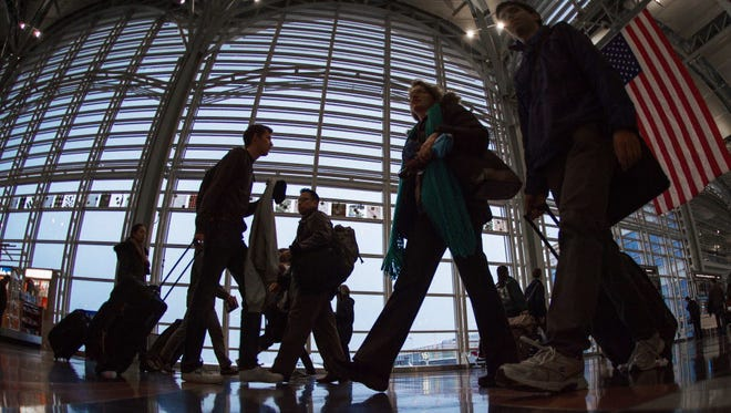 Airline travelers at Ronald Reagan National Airport in Arlington, Va., walk to a Transportation Security Administration checkpoint before traveling on Nov. 26.