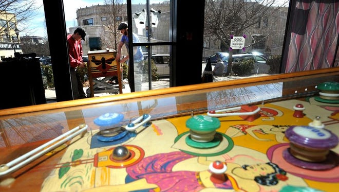 TC DiBella, left, and Lucas Jones of the Asheville Pinball Museum move vintage pinball machines into its expanded space at 1 Battle Square Monday. The new space is about 100 feet east from the current space.