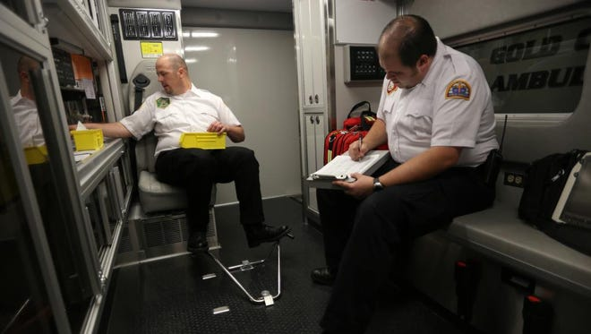 With the Gold Cross Ambulance logo visible in the window behind him, Gold Cross Ambulance paramedic, Andy Rhodes, right and advanced EMT Zack Hansen work on checking the supplies inside one of the new ambulances brought in to service Washington County Tuesday, April 9, 2013 in St. George.