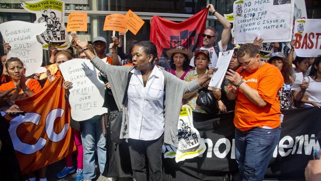 Delsenia Glover, center, Alliance for Tenant Power campaign manager, raises her hands during a protest outside the New York governor's office June 24, 2015.