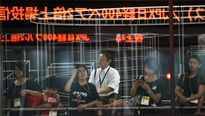 Visitors tour the Tokyo Stock Exchange during a trading session in Tokyo on Aug. 24.