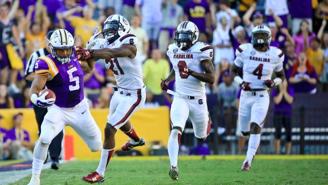 Oct 10, 2015; Baton Rouge, LA, USA; LSU Tigers running back Derrius Guice (5) breaks a tackle by South Carolina Gamecocks safety Isaiah Johnson (21) during the fourth quarter of a game at Tiger Stadium. LSU defeated South Carolina 45-24. Mandatory Credit: Derick E. Hingle-USA TODAY Sports