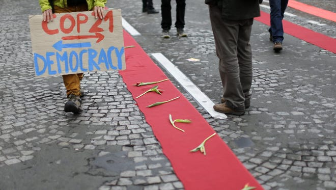 A climate activist holds a placard during a demonstration in Paris, Dec.12, 2015, during the COP21, the United Nations Climate Change Conference.
