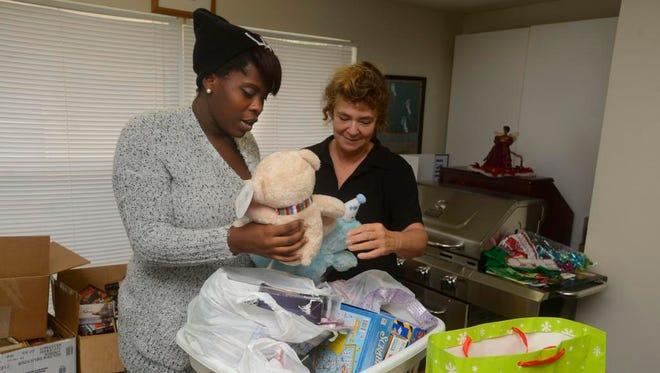 Casey Scott, who volunteers at the Curry House and Sherry Kuss, Lifeskills Coach at Curry House, go through donated goods Sunday at the shelter. Casey, a former homeless teen, is now giving back to the shelter by volunteering after the help she received from the shelter.