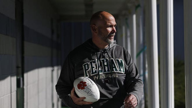 Pelham High School head coach Tom Causey walks out of his office holding a football, in Pelham, Ala. Clemson football head coach Dabo Swinney attended Pelham High School in Alabama and now will play Alabama in the NCAA college football championship game on Monday.