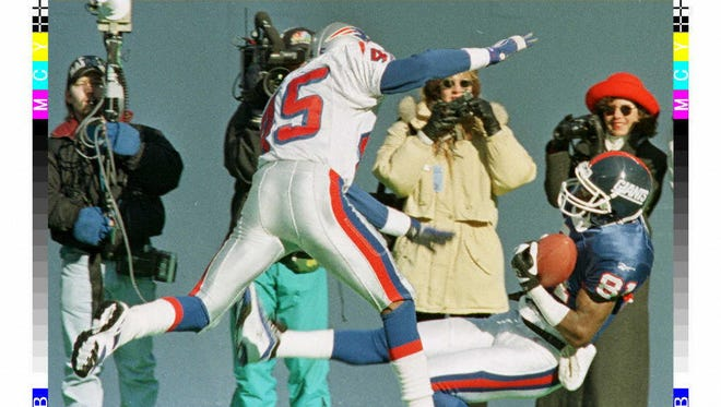 New York Giants' Thomas Lewis (R) catches the ball for a long gain while falling backwards as the New England Patriots' Otis Smith (L) defends in the first quarter at Giants Stadium 21 December.