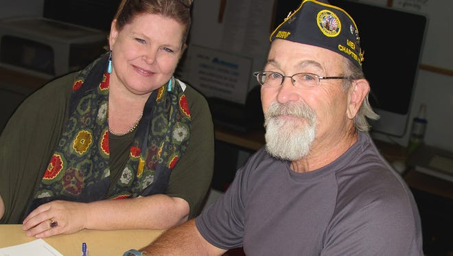Nate Cote, adjutant of Mesilla Valley Disabled American Veterans Chapter 10, signs the Manual Tapia scholarship while Kristi Martin, DACC development officer, looks on.