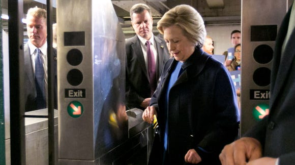 Hillary Clinton holds her MetroCard as she goes through