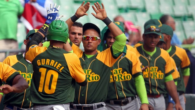 Cuba second baseman Yulieski Gurriel is congratulated by his teammates after scoring a run in a Caribbean Series baseball game in 2015.