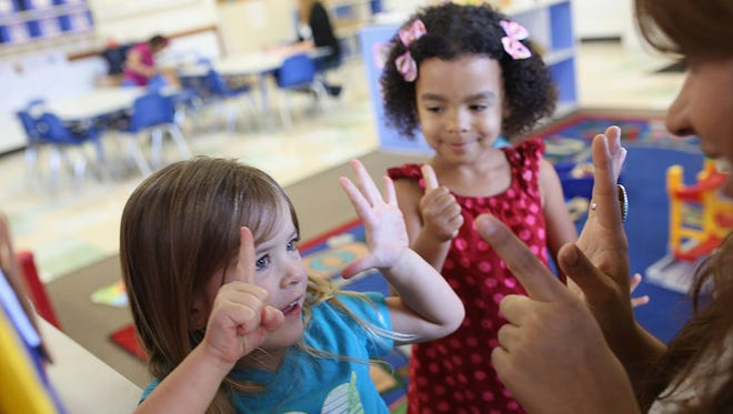 Pre-K students interact with a teacher.