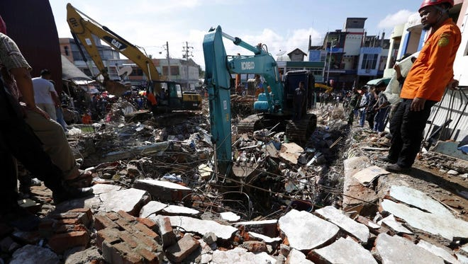 Indonesian rescuers use excavators on Dec. 8 as part of their efforts in the search for victims under the rubble of collapsed buildings after an earthquake hit the region the previous day, in Pidie Jaya district, Aceh, Indonesia.