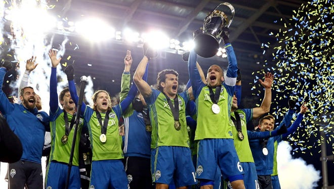 The Seattle Sounders celebrates with Philip F. Anschutz Trophy after beating Toronto FC to win the MLS Cup.