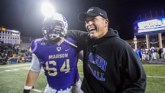 James Madison offensive lineman Matt Frank (64) celebrates with head coach Mike Houston after a game against Sam Houston State. The Dukes will play for the FCS title.