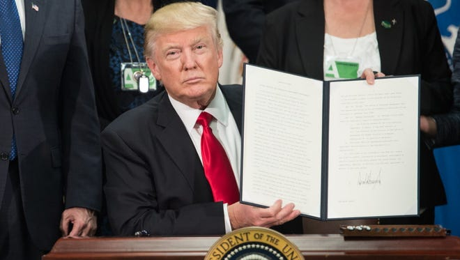 President Trump shows his executive order on Jan. 25, 2017.