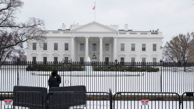 A uniformed Secret Service officer stands outside the north fence of the White House after winter storm Stella left a few inches of snow Tuesday.