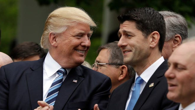 President Donald Trump talks to House Speaker Paul Ryan of Wisconsin in the Rose Garden of the White House on Thursday after the House pushed through a health care bill.