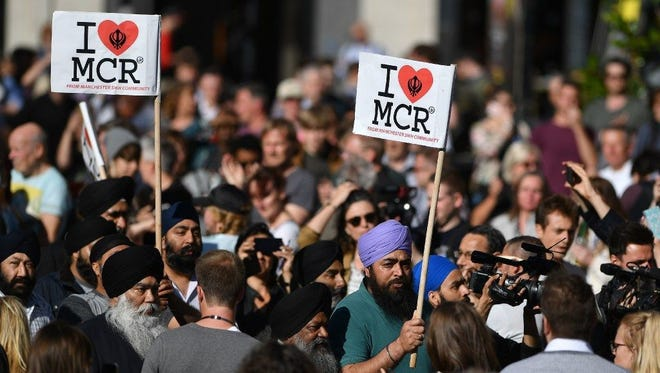 """People from the Manchester Sikh community carry """"I love MCR"""" banners as they arrive to attend a vigil in Albert Square in Manchester, on May 23."""