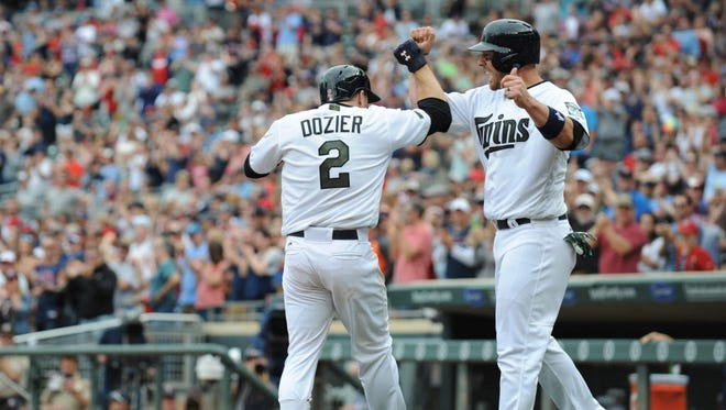 The Twins' Brian Dozier, left, celebrates his home run with Robbie Grossman, right, during the eighth inning against the Rays at Target Field in Minnesota.