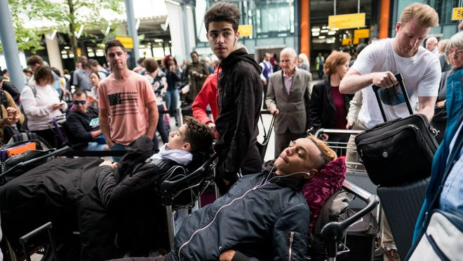 People rest on their luggage outside Heathrow Airport Terminal 5 on May 28, 2017, in London.
