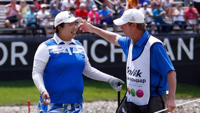 Shanshan Feng, left, hugs her caddie after putting out on the 18th green to win the LPGA Volvik Championship at Travis Pointe Country Club in Ann Arbor, Mich.