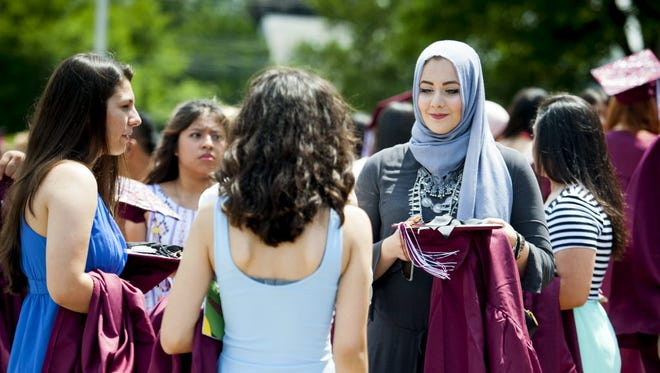 """Clifton Friday 6/26/15 Clifton High School senior Abrar Shahin, far right, was awarded """"best dressed"""" in the class of 2015. Shahin mingles with friends prior to graduation on Friday afternoon."""