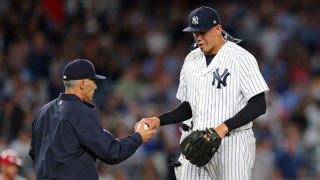 Yankees right-hander Dellin Betances hands the ball to manager Joe Girardi after giving up a run in the eighth inning of Tuesday's 4-2 win over the Reds at Yankee Stadium.