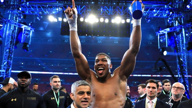 Anthony Joshua celebrates with after beating Wladimir Klitschko in the IBF, WBA and IBO heavyweight title bout at Wembley Stadium on May 1.