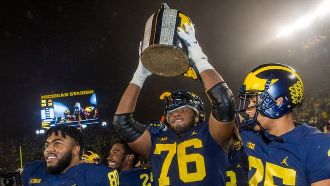 Little Brown Jug: Michigan offensive lineman Juwann Bushell-Beatty lifts up the Little Brown Jug trophy, celebrating with teammates Khalid Hill (80) and Benjamin St-Juste (25), after a 33-10 win over Minnesota in Ann Arbor, Mich.