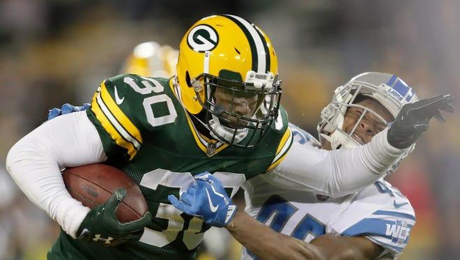 Green Bay Packers running back Jamaal Williams (30) breaks free from Detroit Lions defensive back Charles Washington (45) on Nov. 6, 2017, at Lambeau Field.