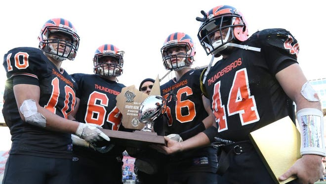 Iola-Scandinavia's Ben Cady (10), Kellan Wandtke (64), Ethan Olson (66) and Bryce Huettner (44) pose with the state runner-up trophy Thursday at the Camp Randall Stadium in Madison.
