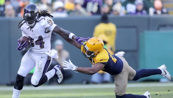 Baltimore Ravens running back Alex Collins stiff arms a Green Bay Packers defender on Nov. 19, 2017, at Lambeau Field.