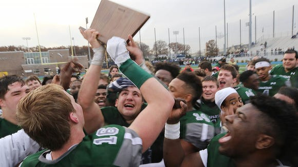 DePaul fullback Vinny DePalma looking up at this team's trophy after the game.