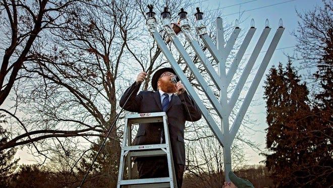 Rabbi Mordechai Baumgarten lights the menorah at Picatinny Arsenal, in Rockaway Township.