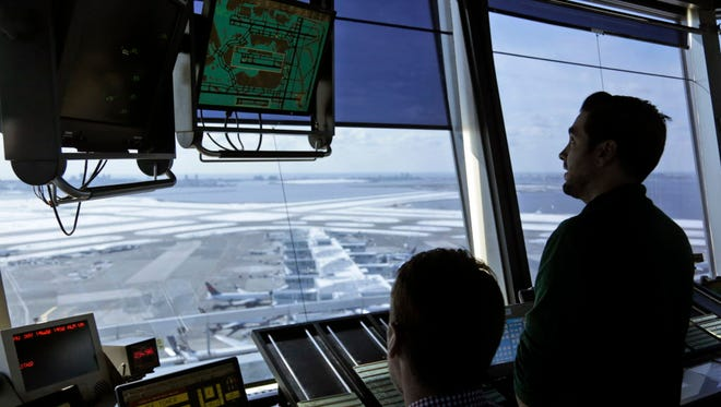 In this March 16, 2017, photo, air traffic controllers work in the tower at John F. Kennedy International Airport in New York.