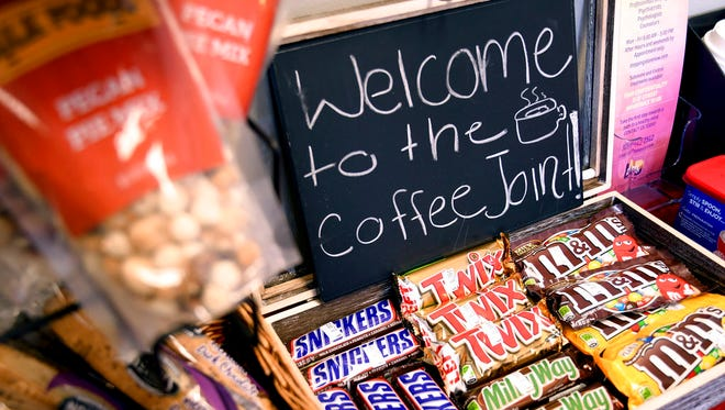 In this Feb. 9, 2018 file photo, a welcome sign greets customers at the Coffee Joint in Denver. The business only serves snacks and coffee currently, but its owners want to create a space where people can vape or use edible marijuana. A Denver attorney recommended on Wednesday, Feb. 14, that the city approve the proposal, based on a public hearing held Friday. The city of Denver's top licensing regulator has the final say on issuing the permit.